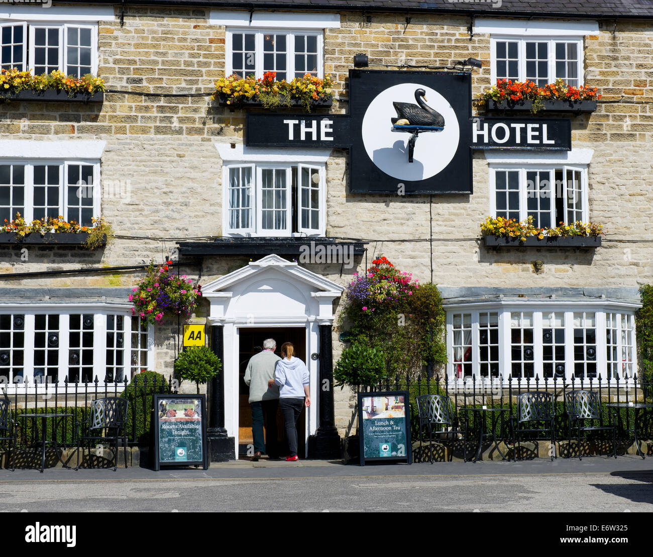 Man and woman walking into the Black Swan Hotel, Helmsley, North Yorkshire, England UK - Stock Image