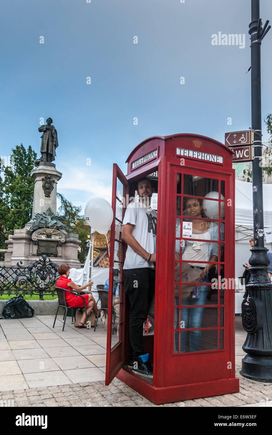 BT Red Telephone Box and Monument to Adam Mickiewicz, Warsaw, Poland - Stock Image