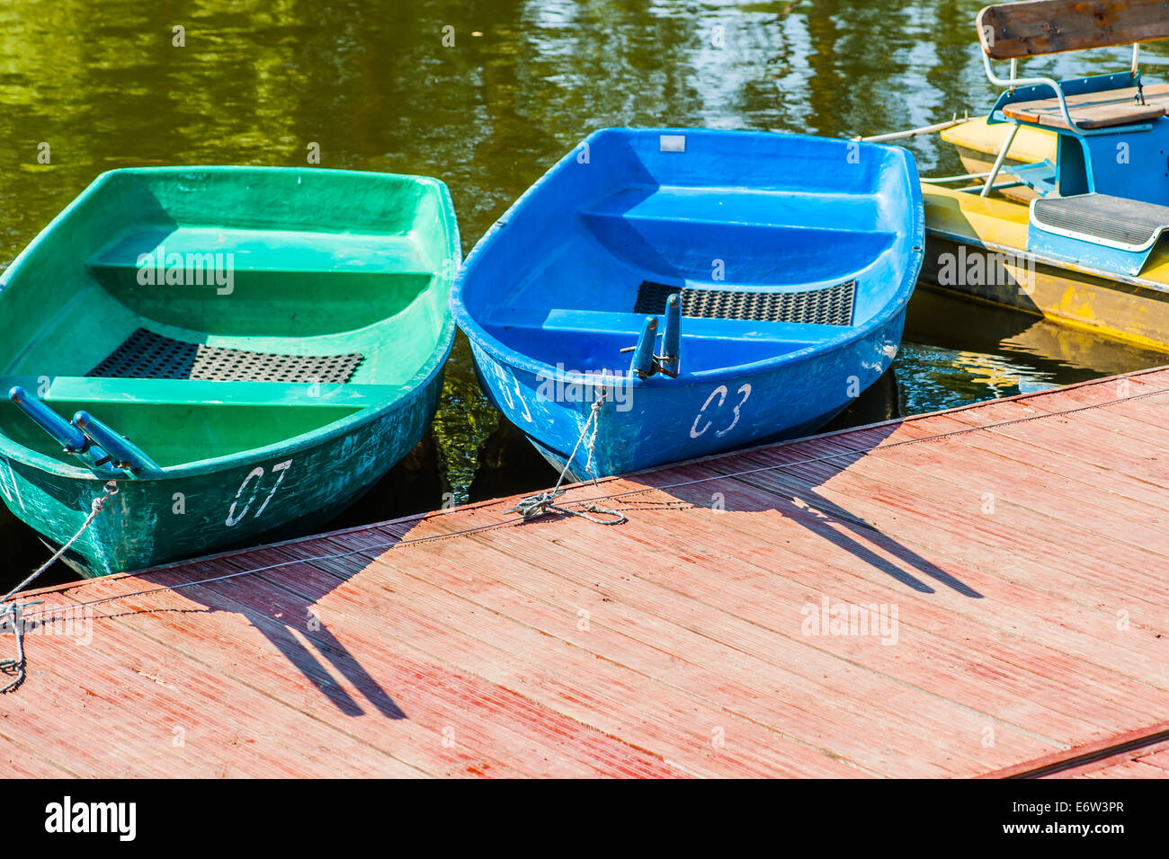Oar boats and pedal boat for hire wait for clients - Stock Image