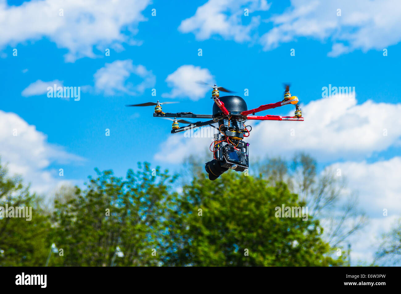 Closeup view of a hexacopter with photo camera attached in low altitude flight - Stock Image