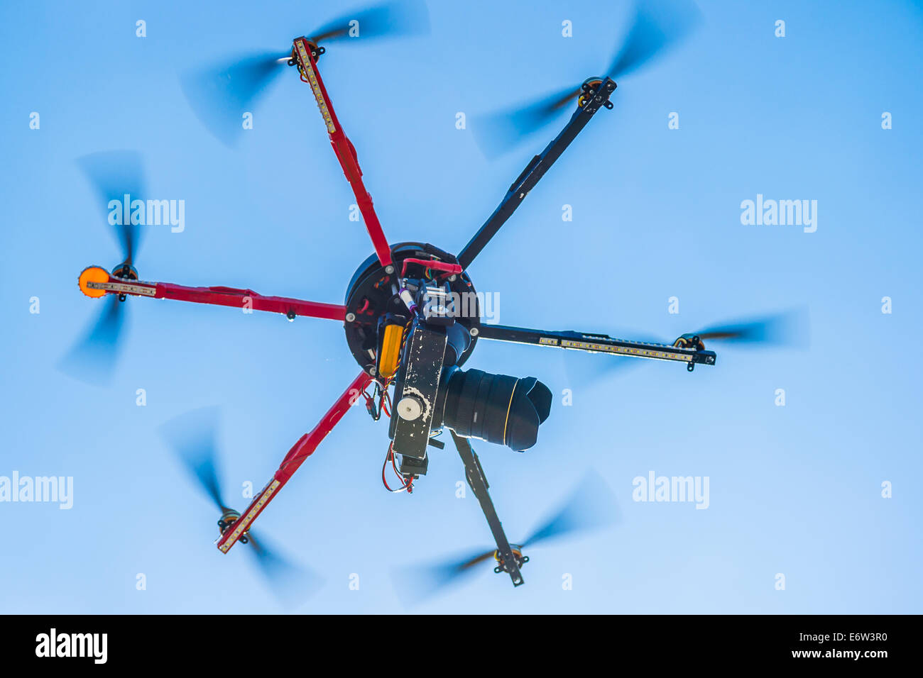 Closeup view of a hexacopter with photo camera attached in flight - Stock Image