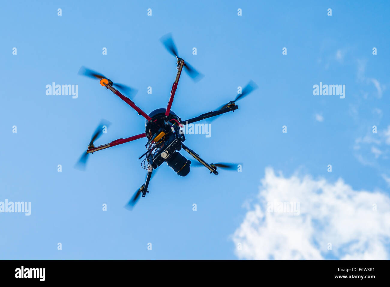 Hexacopter with photo camera attached in flight - Stock Image