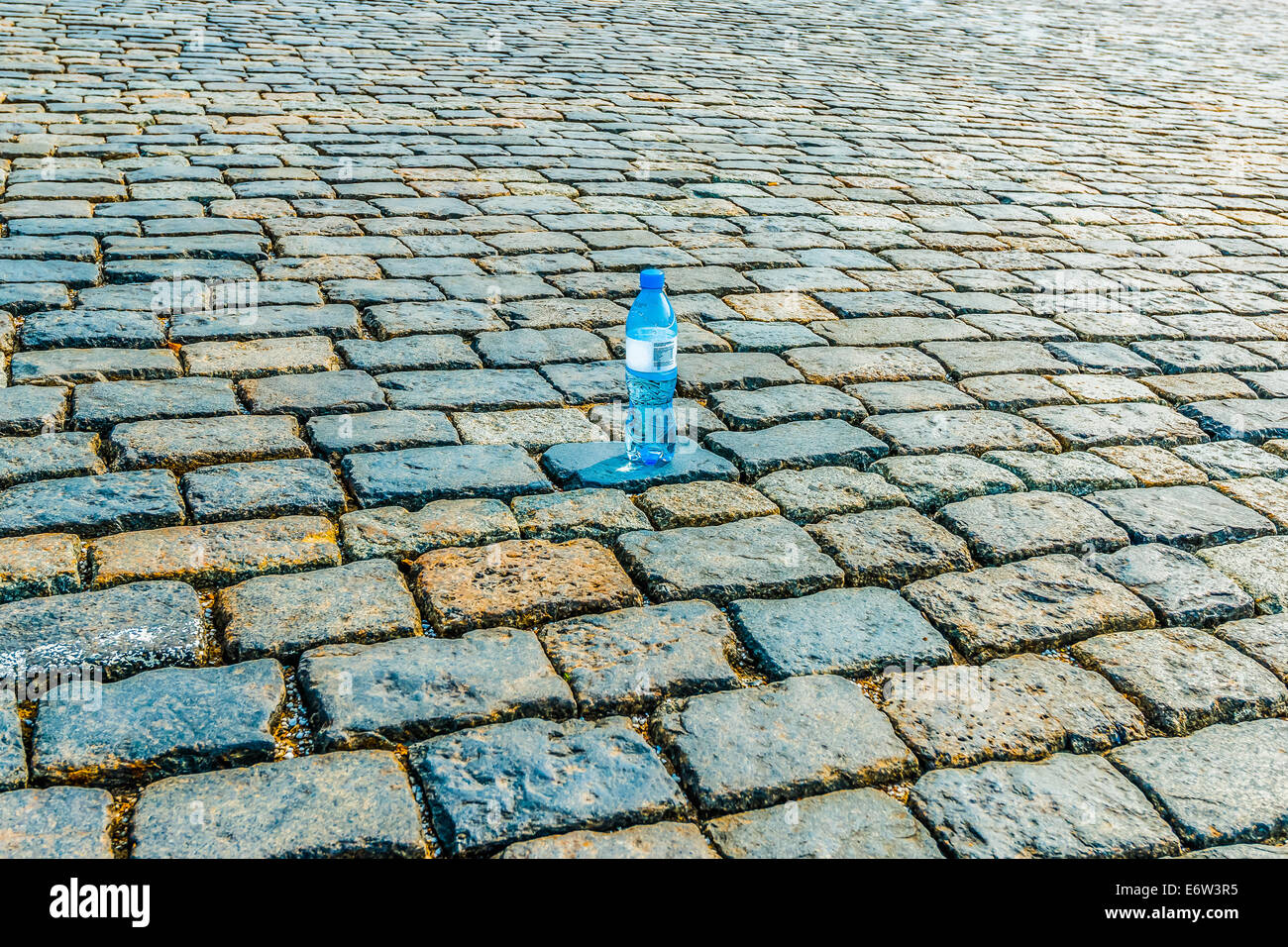 Lonely bottle of clear potable water on the torrid cobble paved ground - Stock Image