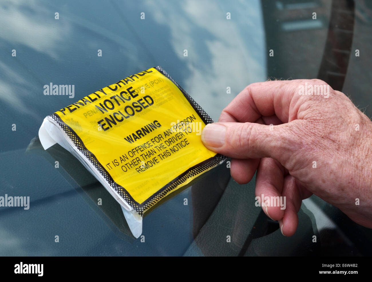 A motorist removing a fixed penalty charge ticket from his windscreen - Stock Image