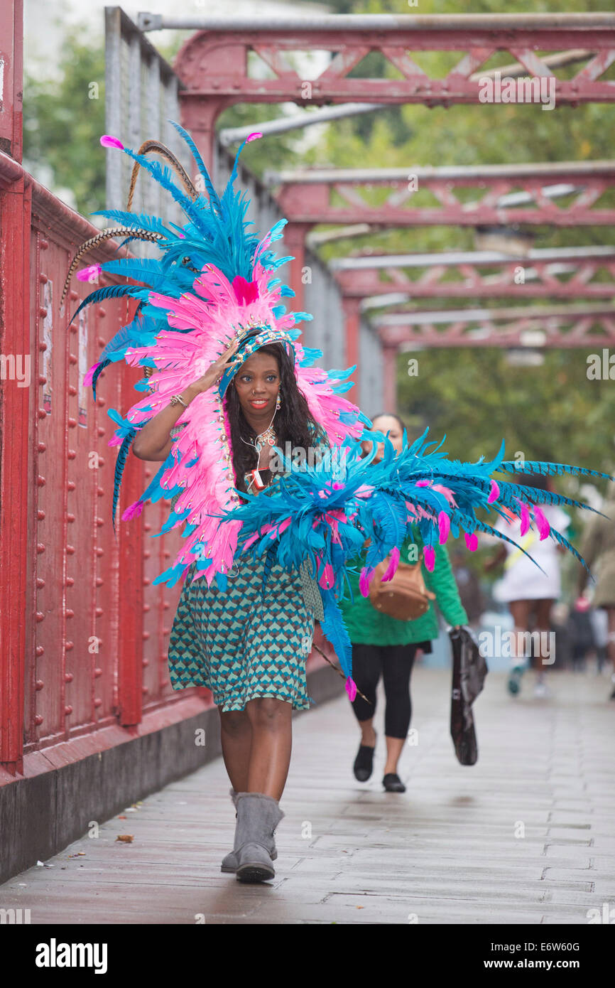 A performer carrying feathers makes her way to the parade at Notting Hill Carnival - Stock Image