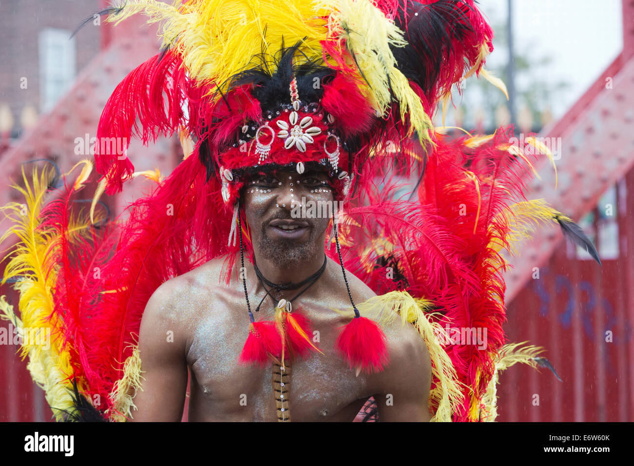 Male Samba Dancer with feathers from the London School of Samba at a rainy Notting Hill Carnival parade, London, - Stock Image