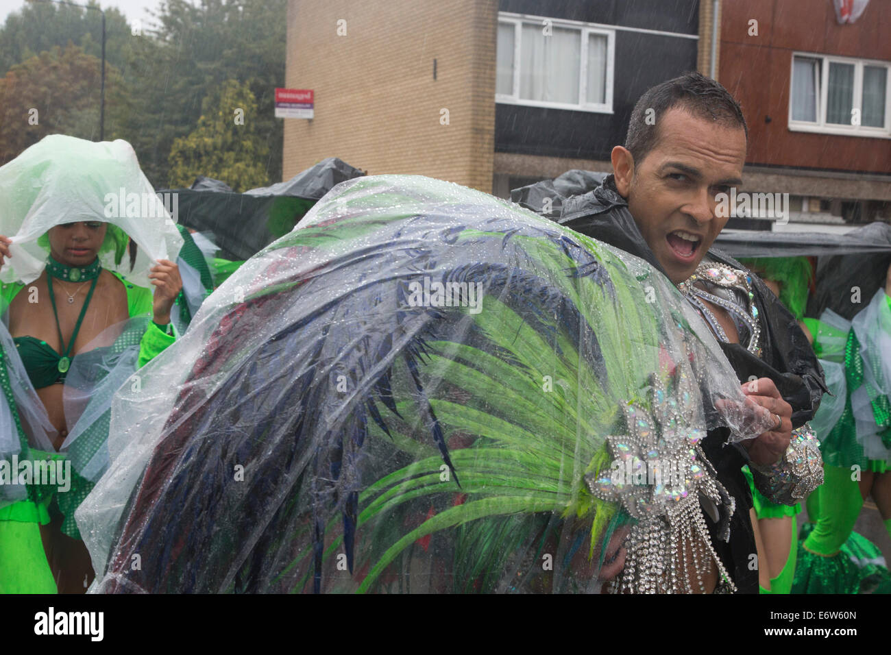 Samba Dancer from the London School of Samba covers his feathers from the rain at the Notting Hill Carnival parade - Stock Image