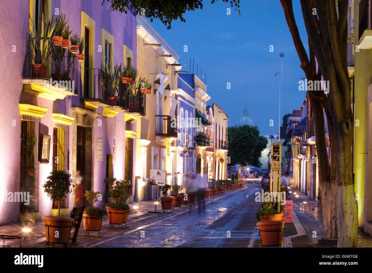 A couple walks down Calle de los Sapos at twilight in Puebla, Mexico - Stock Image