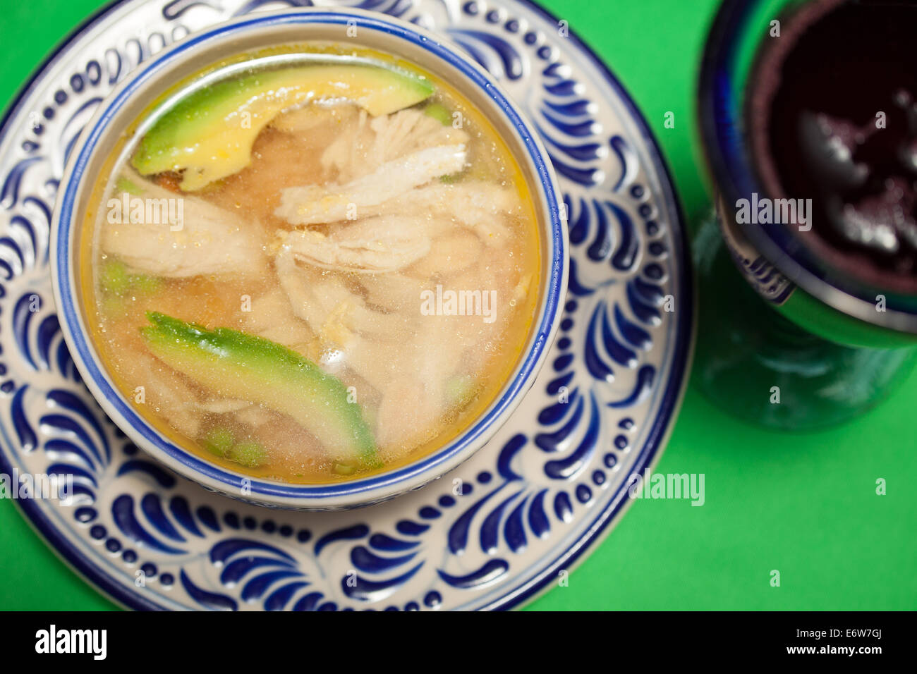 Chicken soup with avocado slices on a talavera plate in Puebla, Mexico. - Stock Image