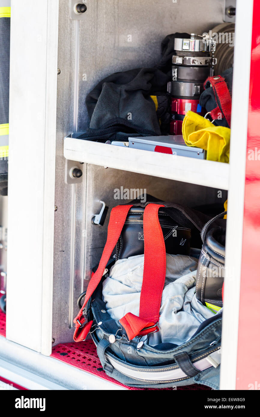 Firefighter clothing hanging on fire truck. - Stock Image
