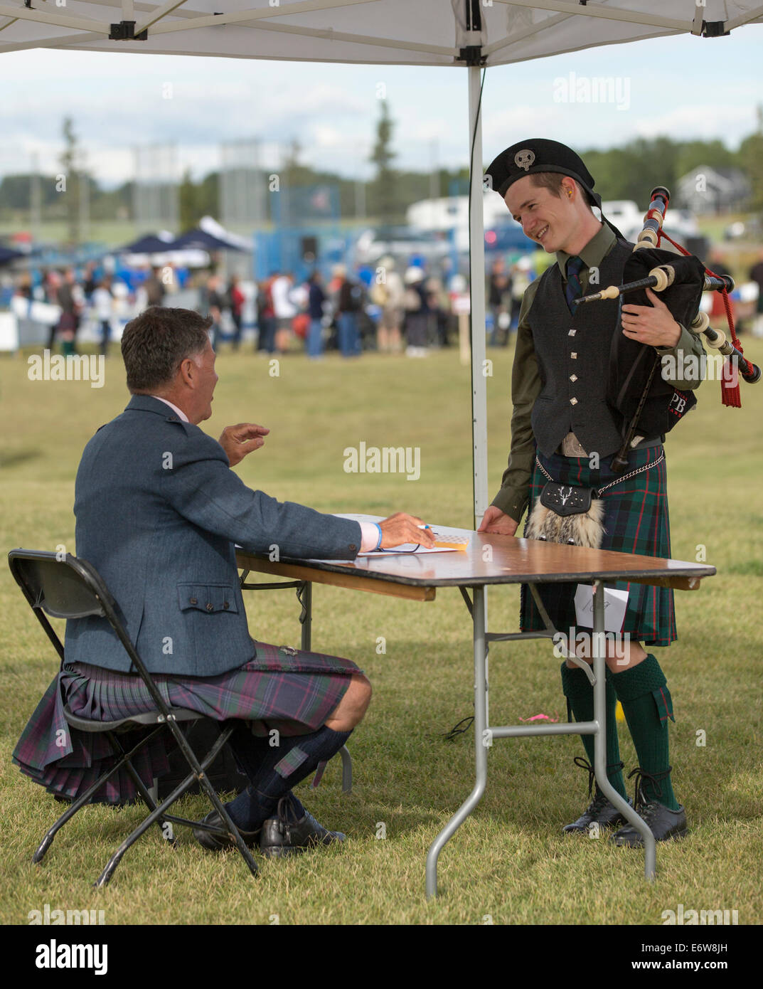 Calgary, Alberta, Canada. 30th Aug, 2014. Judge speaks with bagpipe competitor at the Calgary Highland Games, Calgary, - Stock Image