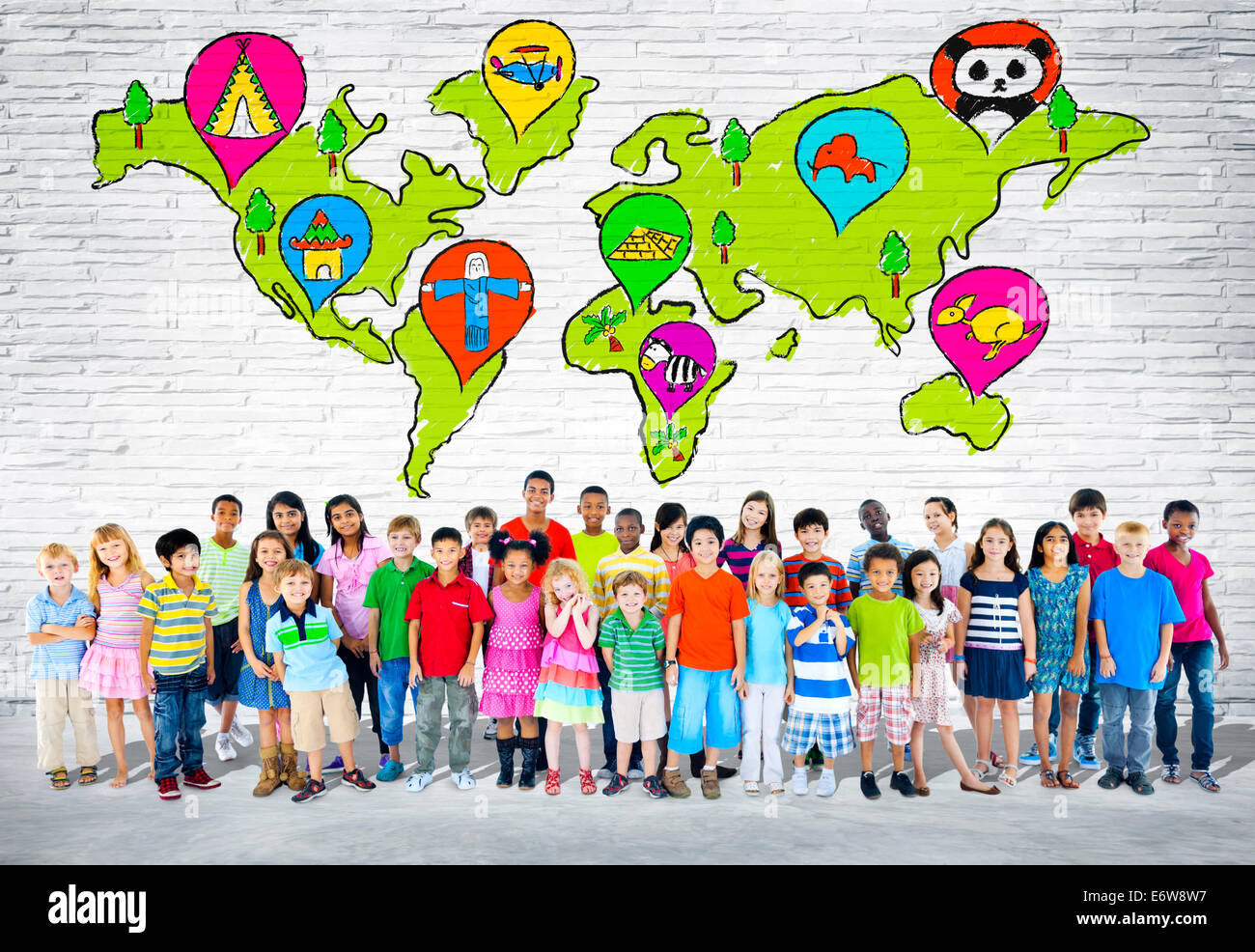 Group of elementary aged children standing in front of a wall of world cartography. - Stock Image