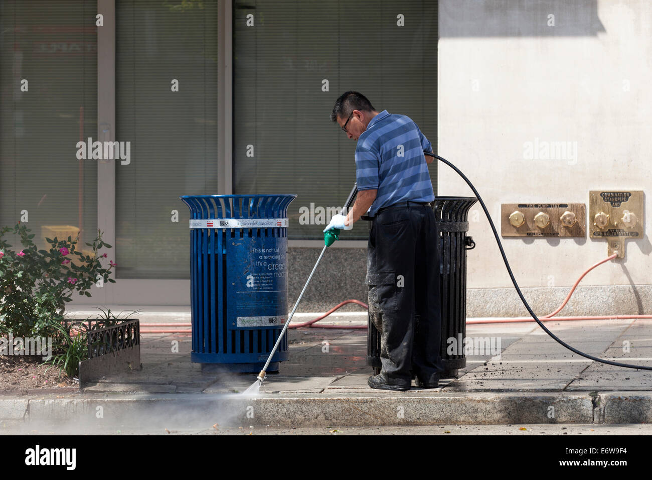 Man pressure washing sidewalk - USA - Stock Image