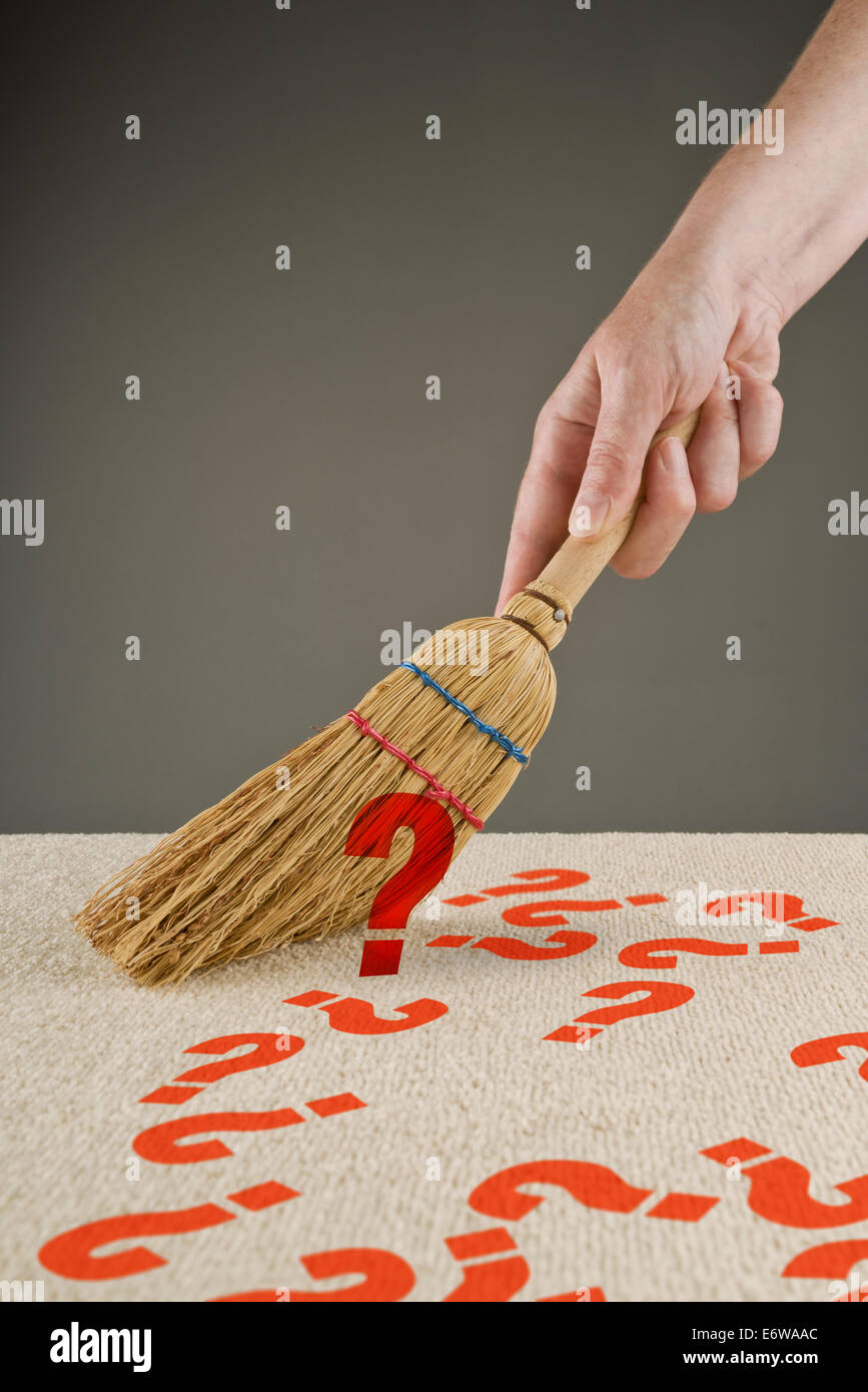Hand sweeping question marks from the floor with small broom - Stock Image