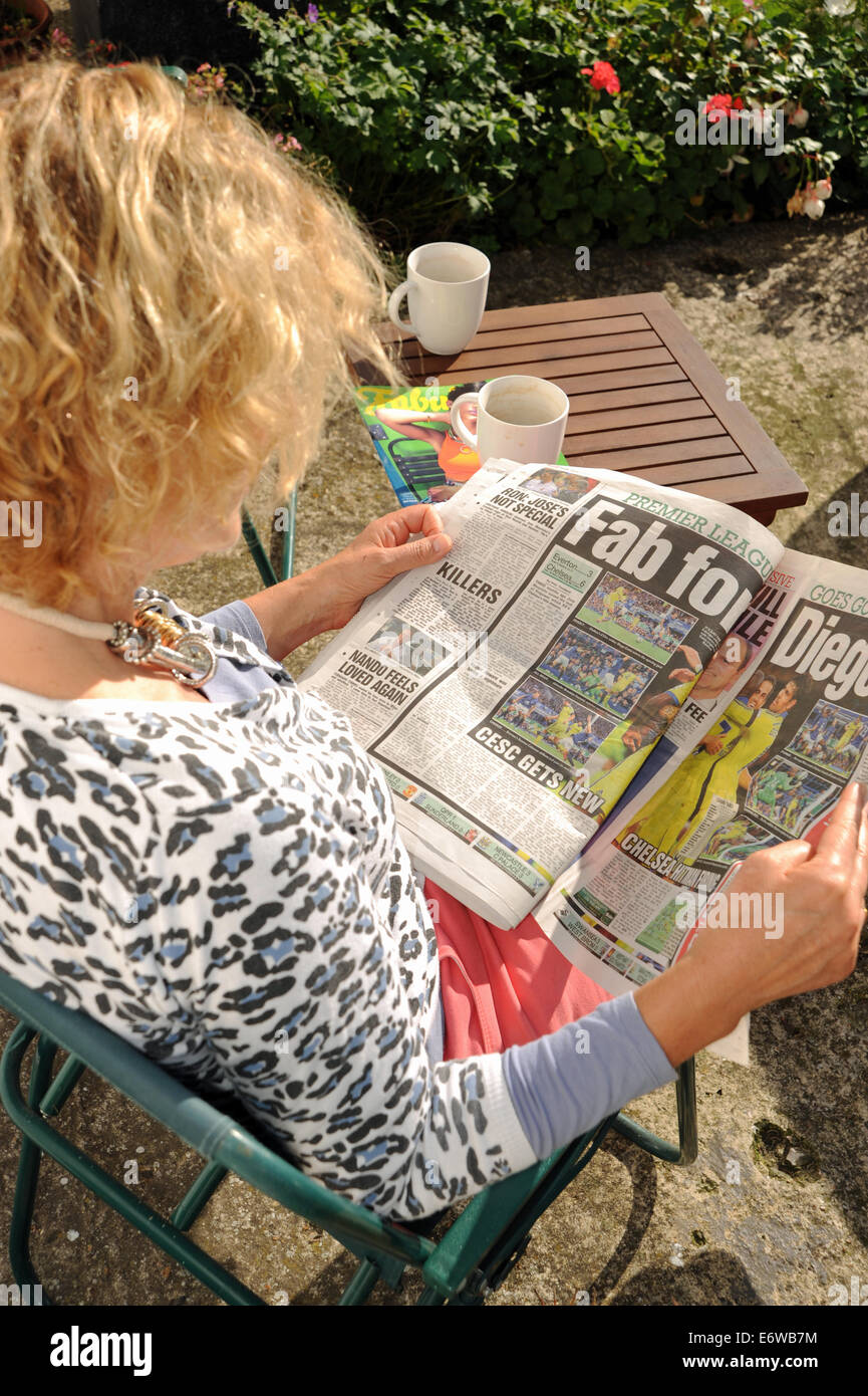 Woman sitting in garden reading the Sun on Sunday red top tabloid newspaper UK Stock Photo