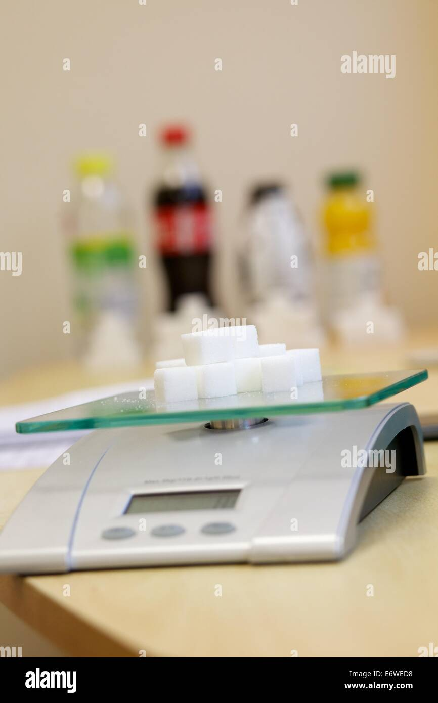 close up image of sugar lumps on a set of weighing scales - Stock Image