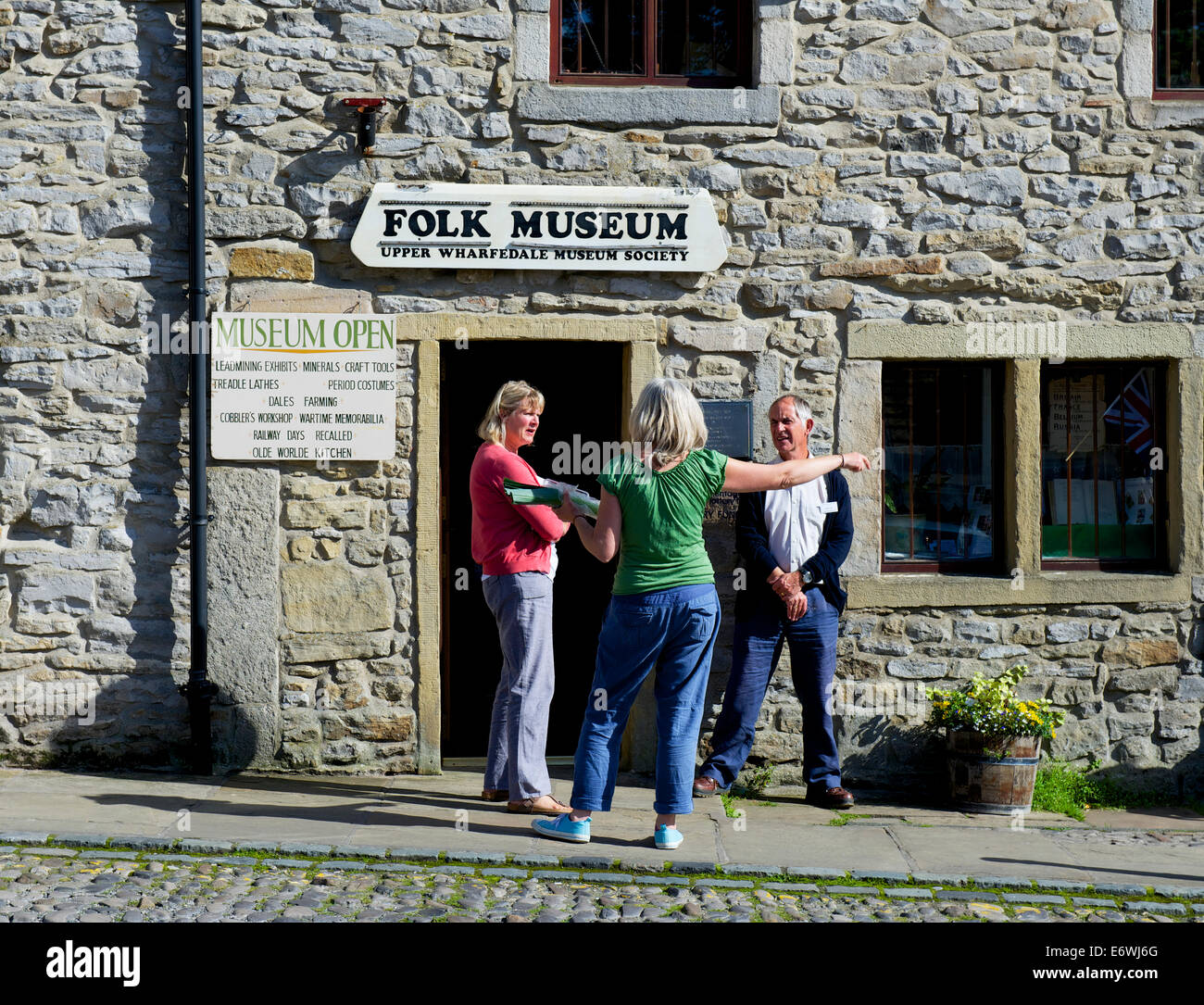 Three people outside the Folk Museum, Grassington, Wharfedale, Yorkshire Dales National Park, North Yorkshire, England - Stock Image