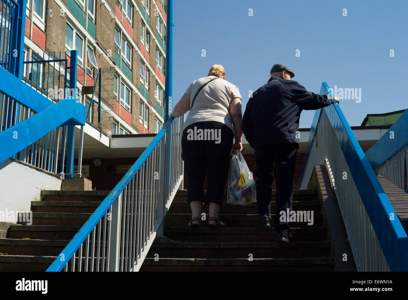 Couple on steps in housing estate. - Stock Image