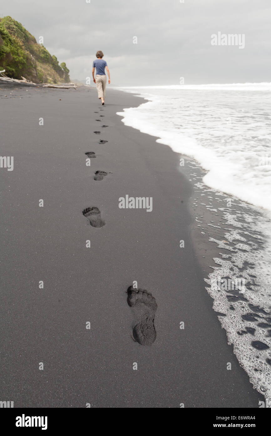 Footprints in black sand, woman walking along the beach, South Island, New Zealand - Stock Image