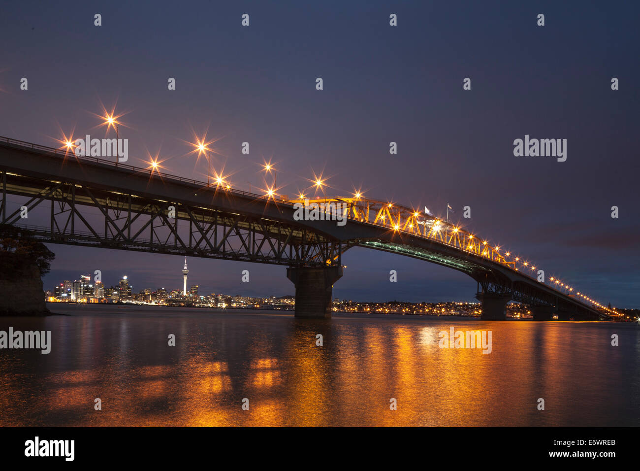 Auckland Harbour Bridge and skyline with Sky Tower in the evening light, Auckland City, North Island, New Zealand - Stock Image