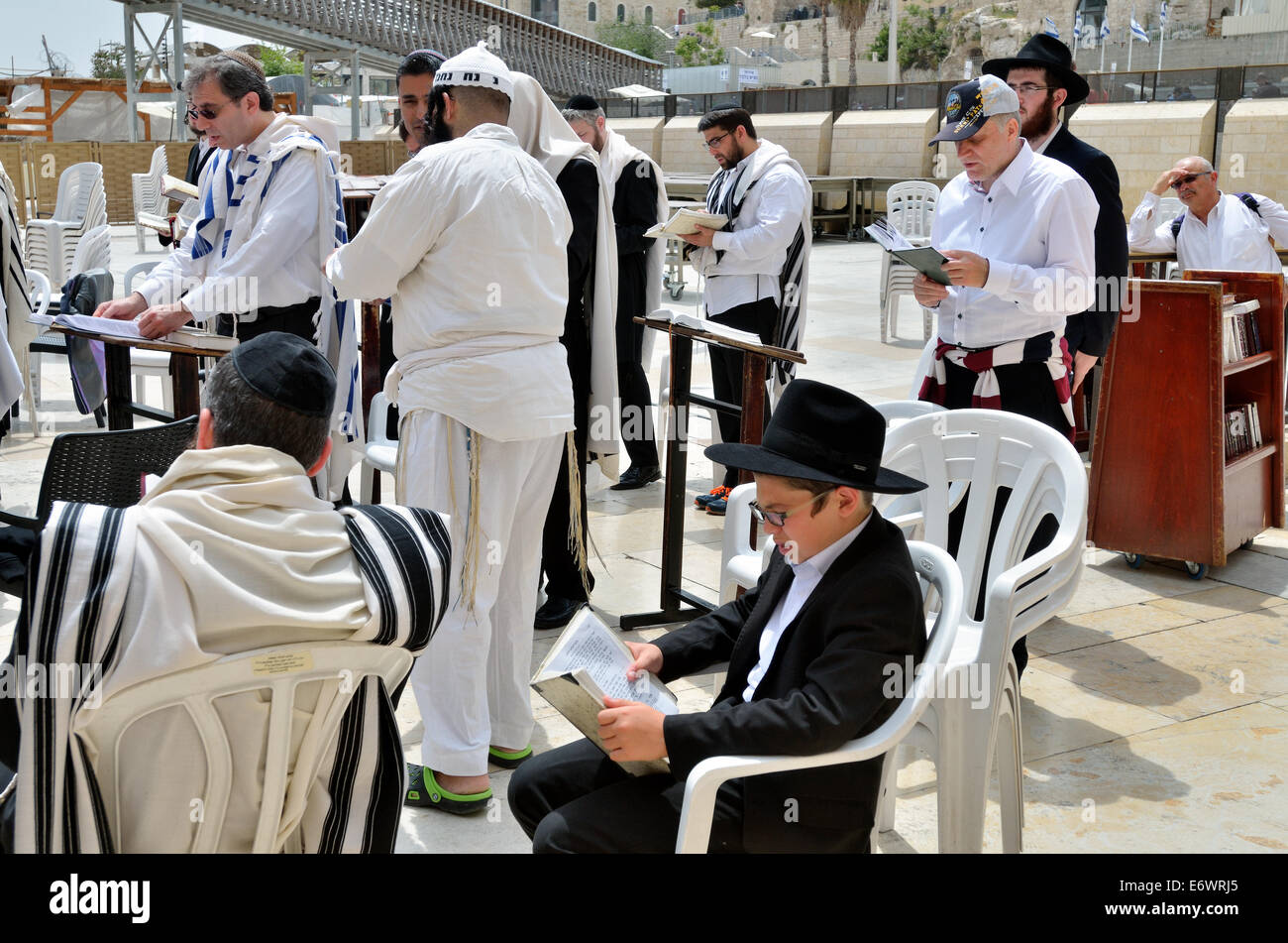 Jews read Torah sitting at the Wailing Wall in the courtyard of the Jews Temple in Old City of Jerusalem, Israel - Stock Image
