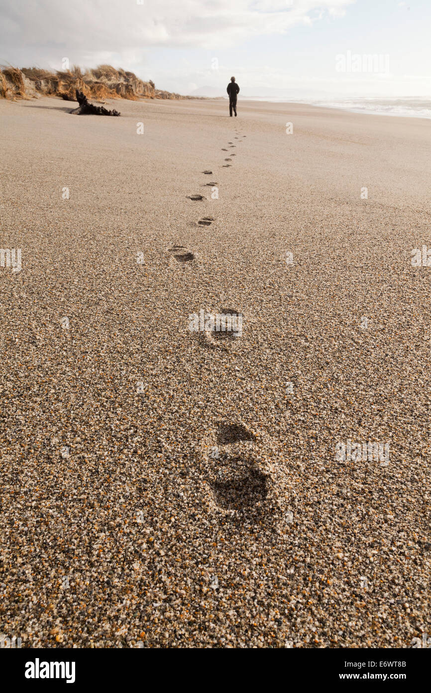 Footprints in coarse sand, person walking along the beach, autumn, South Island, New Zealand - Stock Image