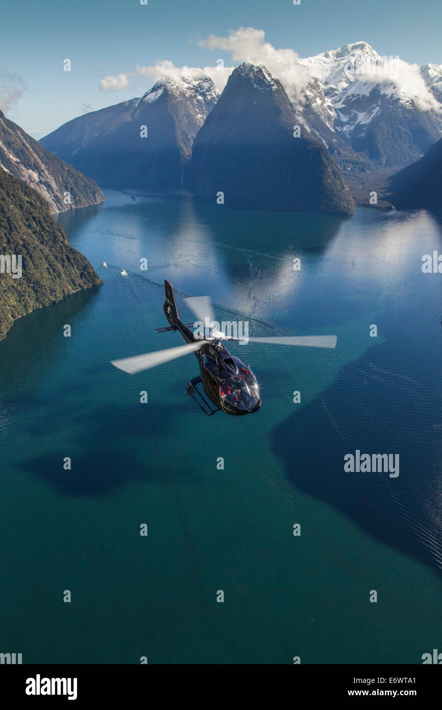 Aerial view of Milford Sound with helicopter below, Mitre Peak, Fiordland National Park, South Island, New Zealand - Stock Image