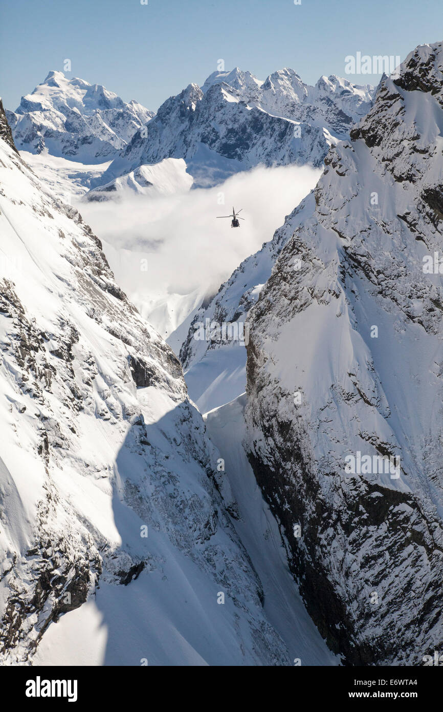 Helicopter flight over snowy mountains, Southern Alps, South Island, New Zealand - Stock Image