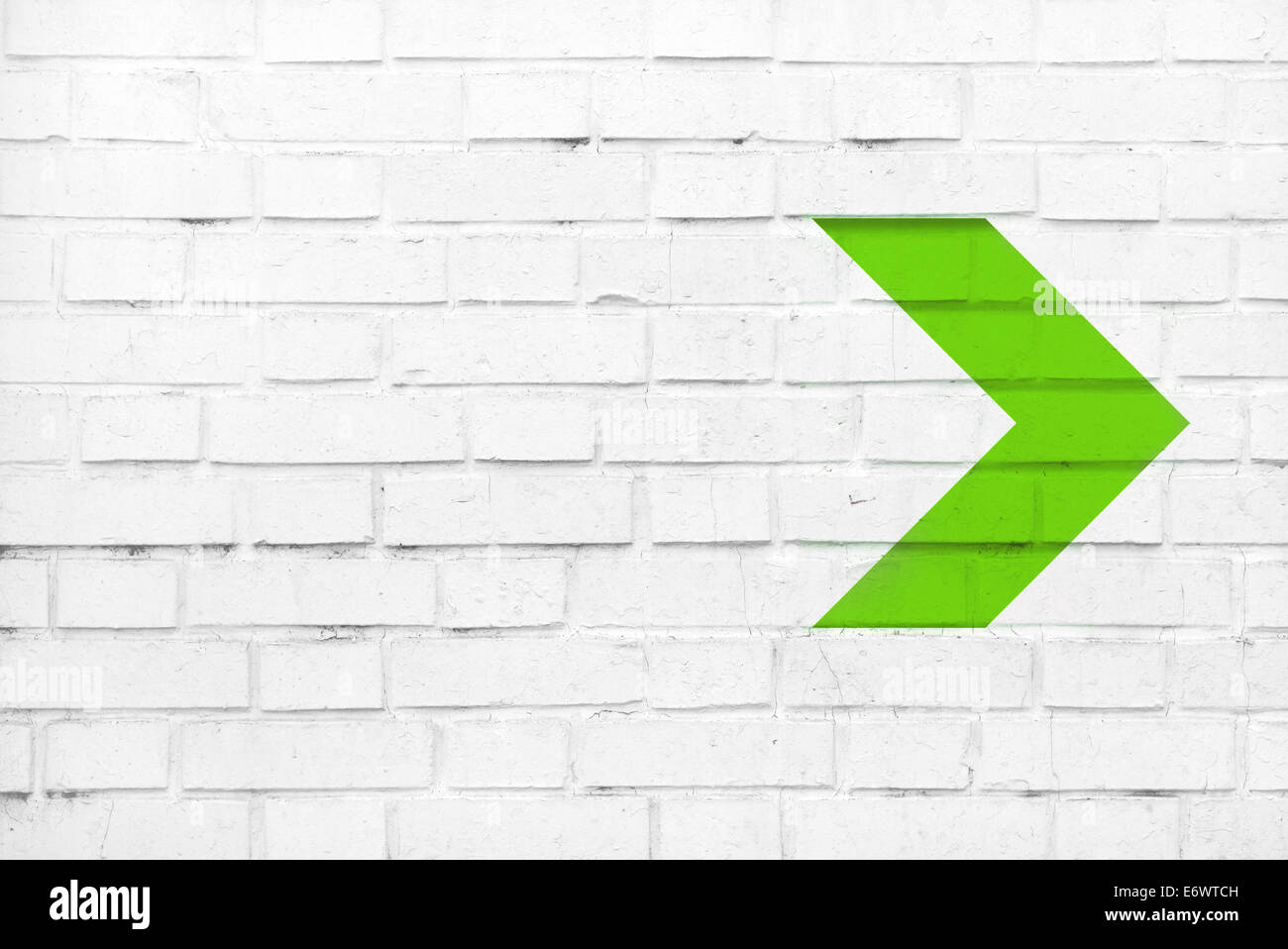 Green arrow on white wall, direction and guidance - Stock Image