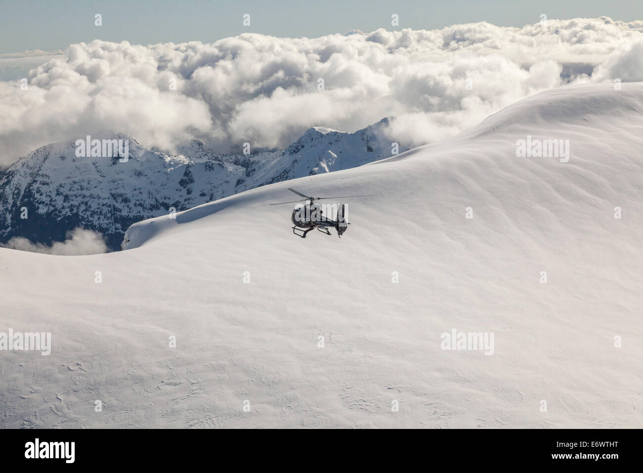 Helicopter flight over snowy mountains, South Island, New Zealand - Stock Image