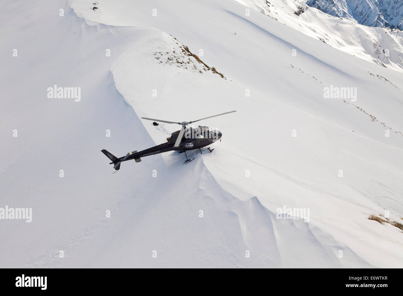 Helicopter landing with skiers and snowboarders in deep snow, Winter sport, Heliskiing, South Island, New Zealand - Stock Image