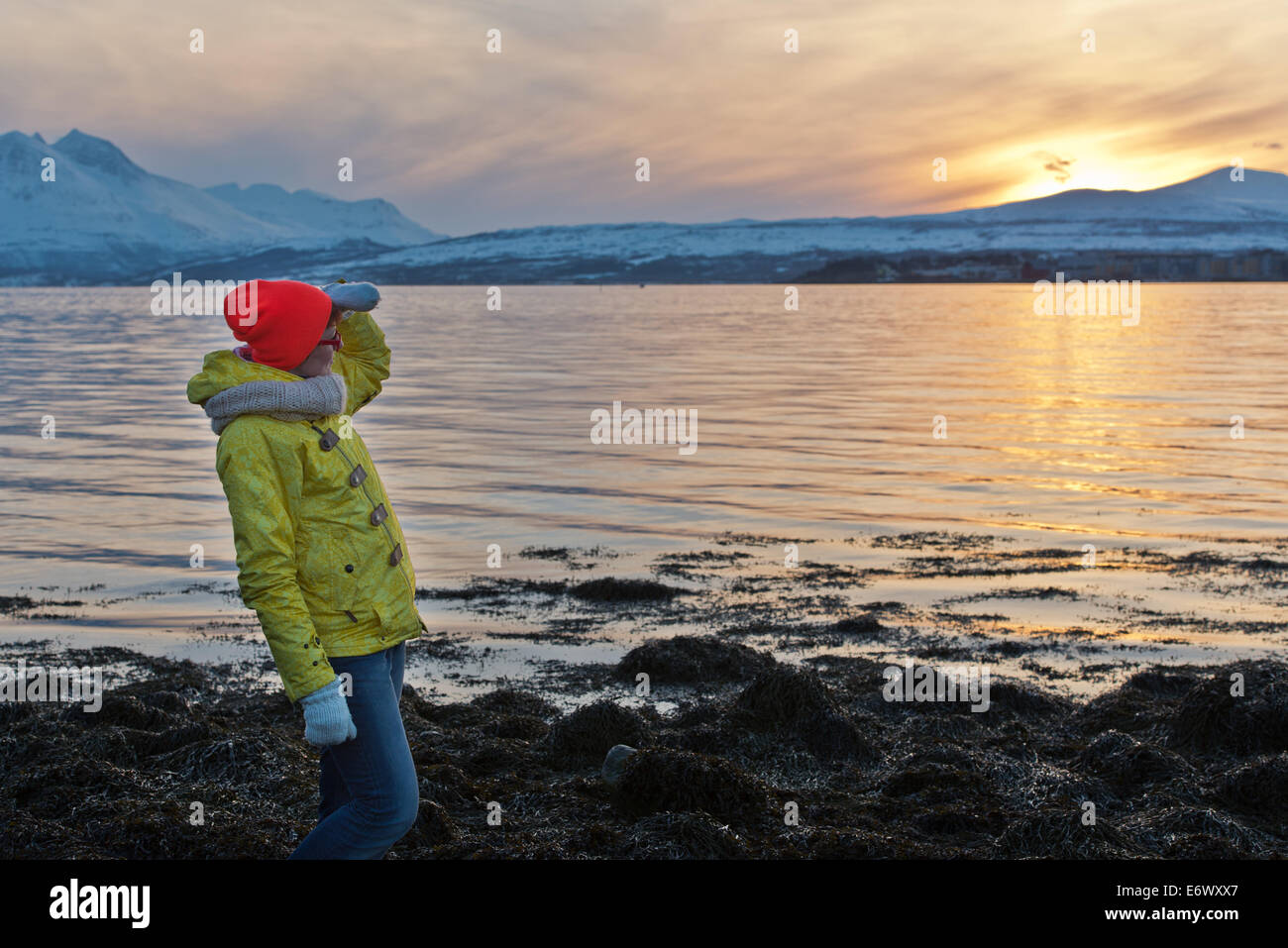 Woman looking ahead with the hand in sunset - Stock Image