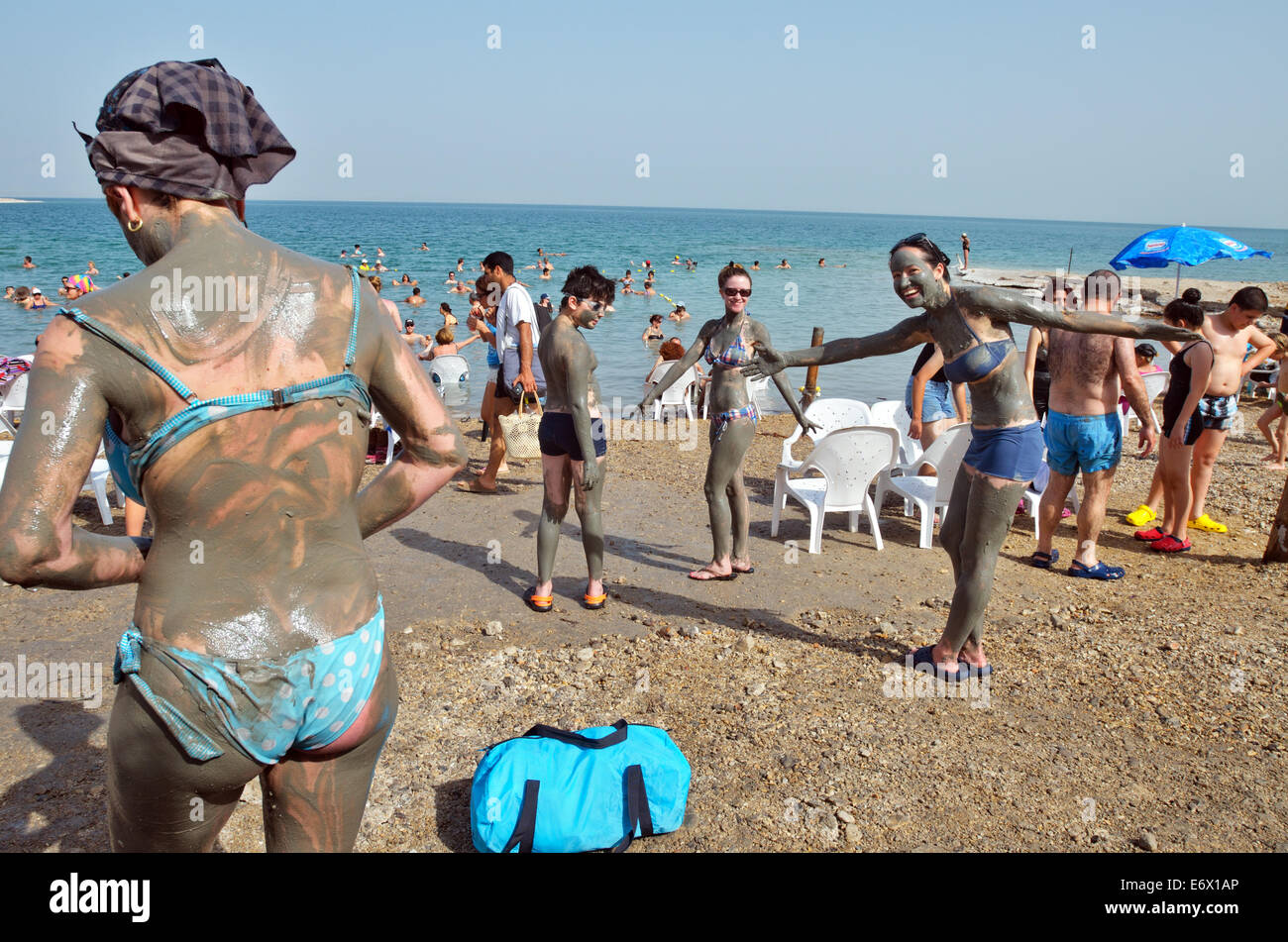People are rubbing themselves with clay on the Dead Sea Coast, Israel - Stock Image