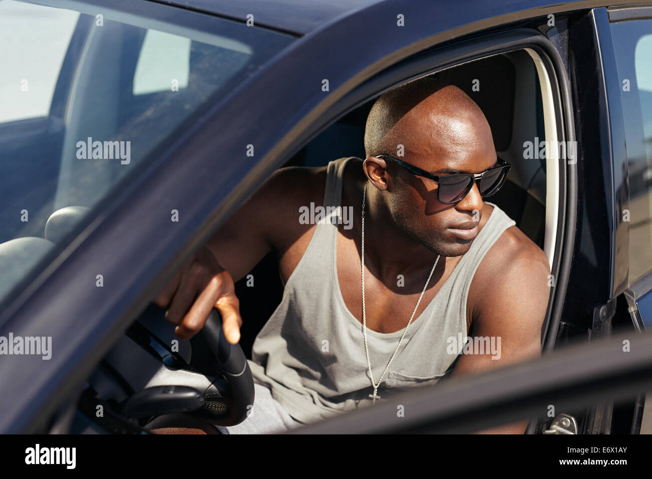Image of young man in car looking away. Stylish African guy on road trip. - Stock Image