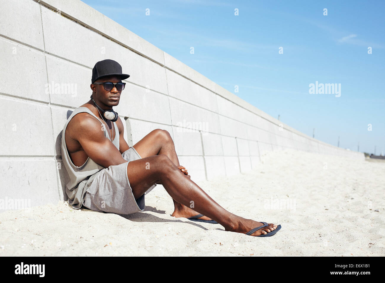 Handsome guy with headphones and sunglasses sitting on beach next to a wall. Muscular African-American male model - Stock Image