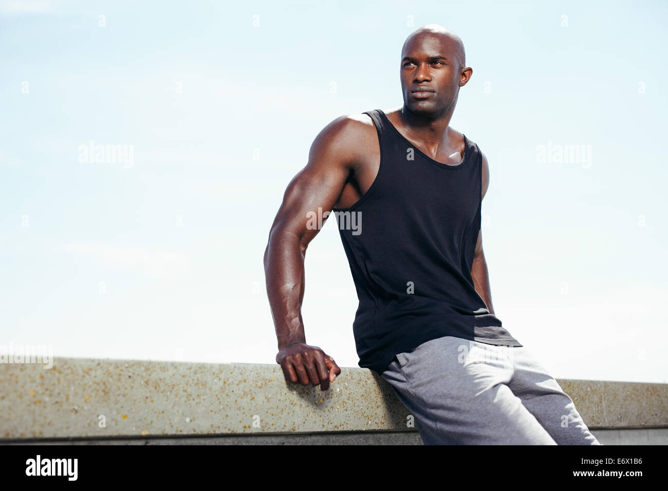 Image of muscular young man sitting outdoors against sky looking away at copyspace. Fit african male model. - Stock Image