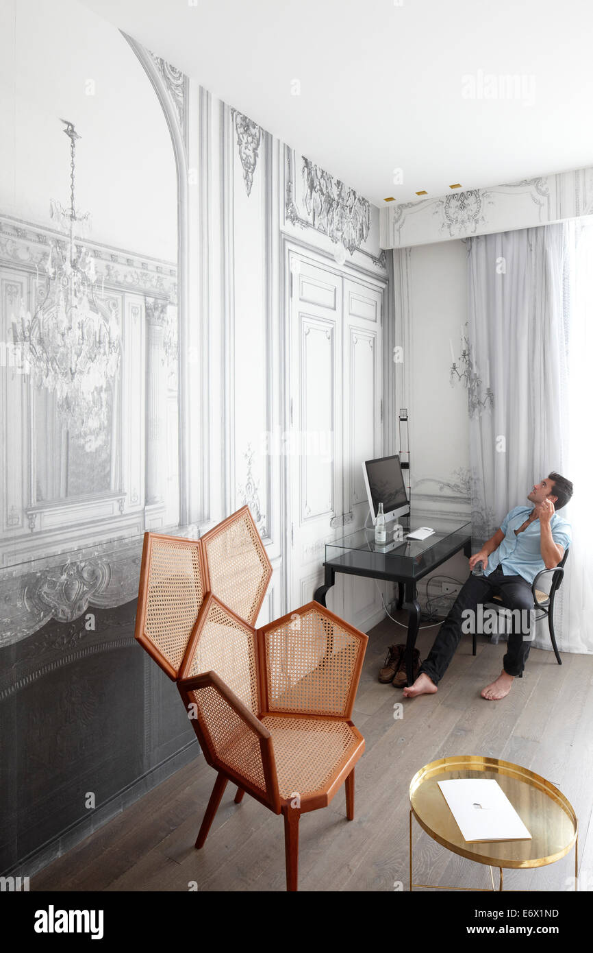 Man sitting at a desk in a hotel suite, Paris, France - Stock Image