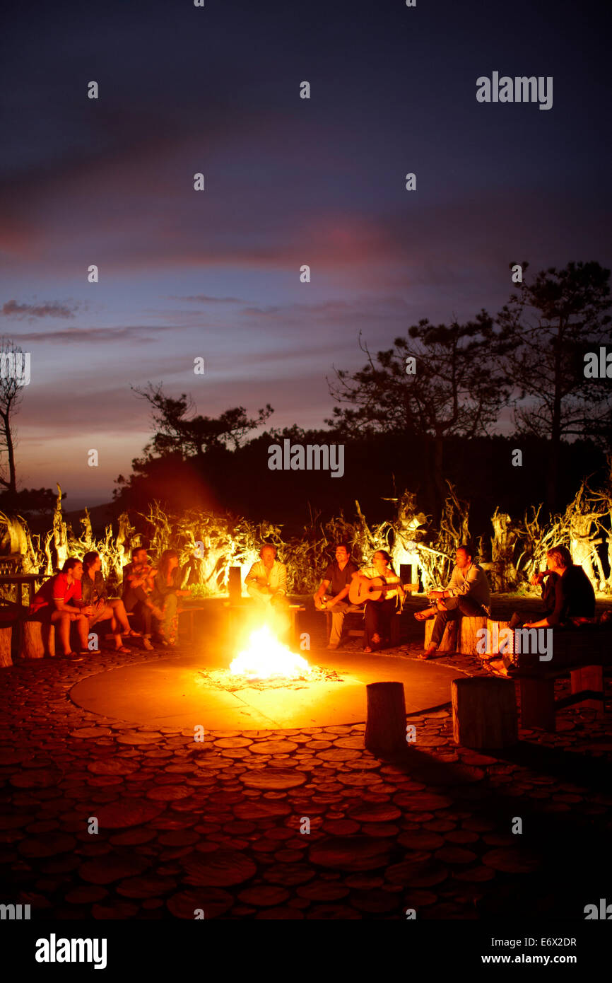 Guests sitting around the camp fire called 'Ring of Fire' in the garden of Hotel Areias do Seixo, Povoa - Stock Image