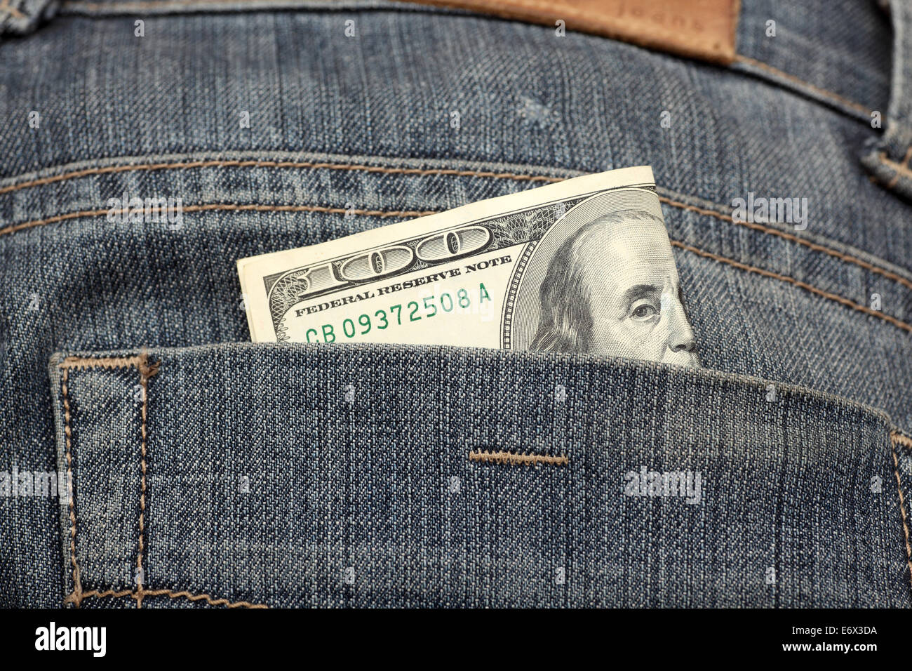 One hundred dollars in the back pocket of jeans. Closeup. - Stock Image