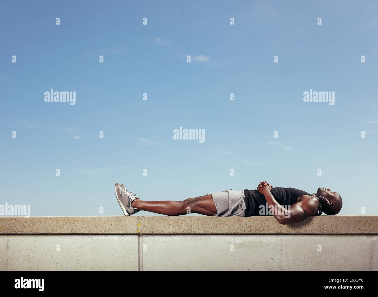 African young man lying on a wall by walkway outdoors with copy space. Muscular young fitness model relaxing after - Stock Image