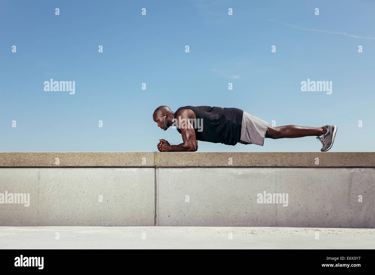Side view of strong young african athlete doing core exercise on a wall by a walkway. Muscular young athlete exercising - Stock Image