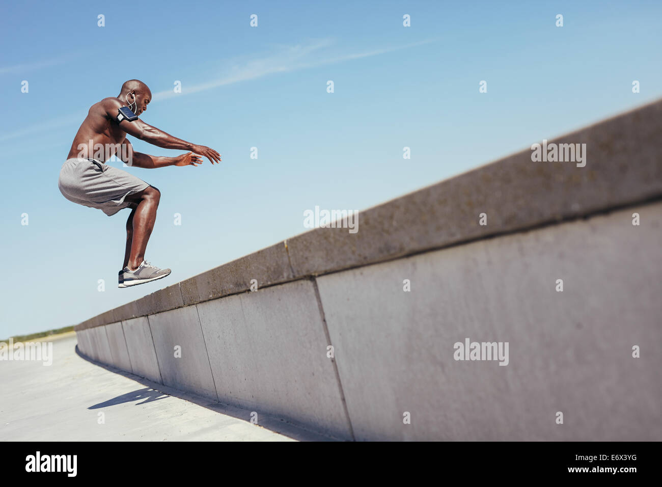 Shirtless african athlete working out on cross fit jump box outside on a wall. Muscular man doing box jumps outdoors. - Stock Image