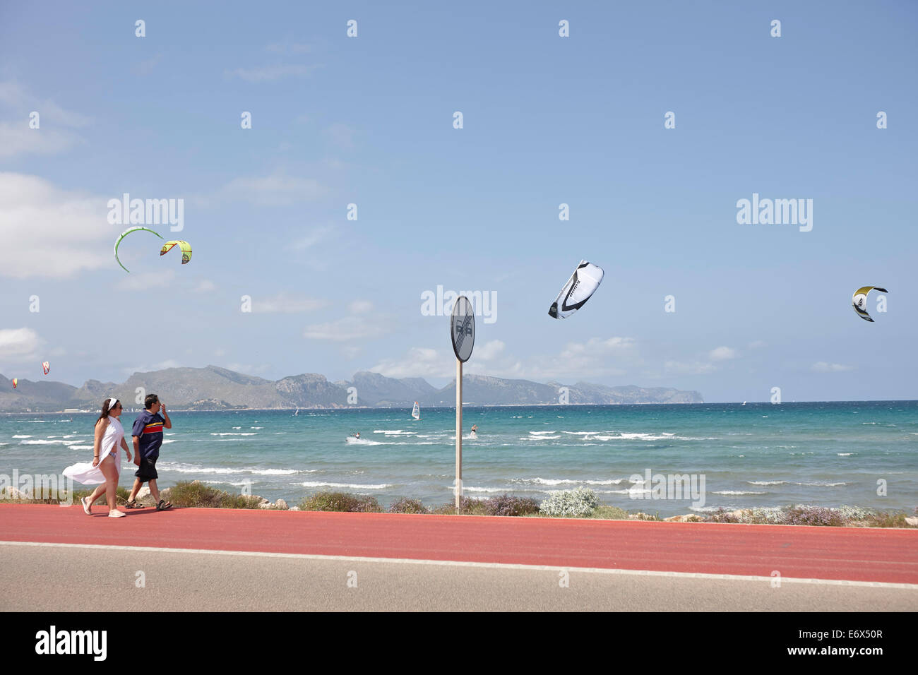 Tourists walking along a bike lane next to the coastal road, kite surfer near Club Pollentia, Badia de Pollenca - Stock Image