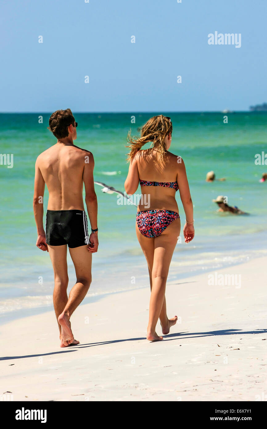 Two young people enjoy a walk along the beach at Anna Maria Island FL - Stock Image