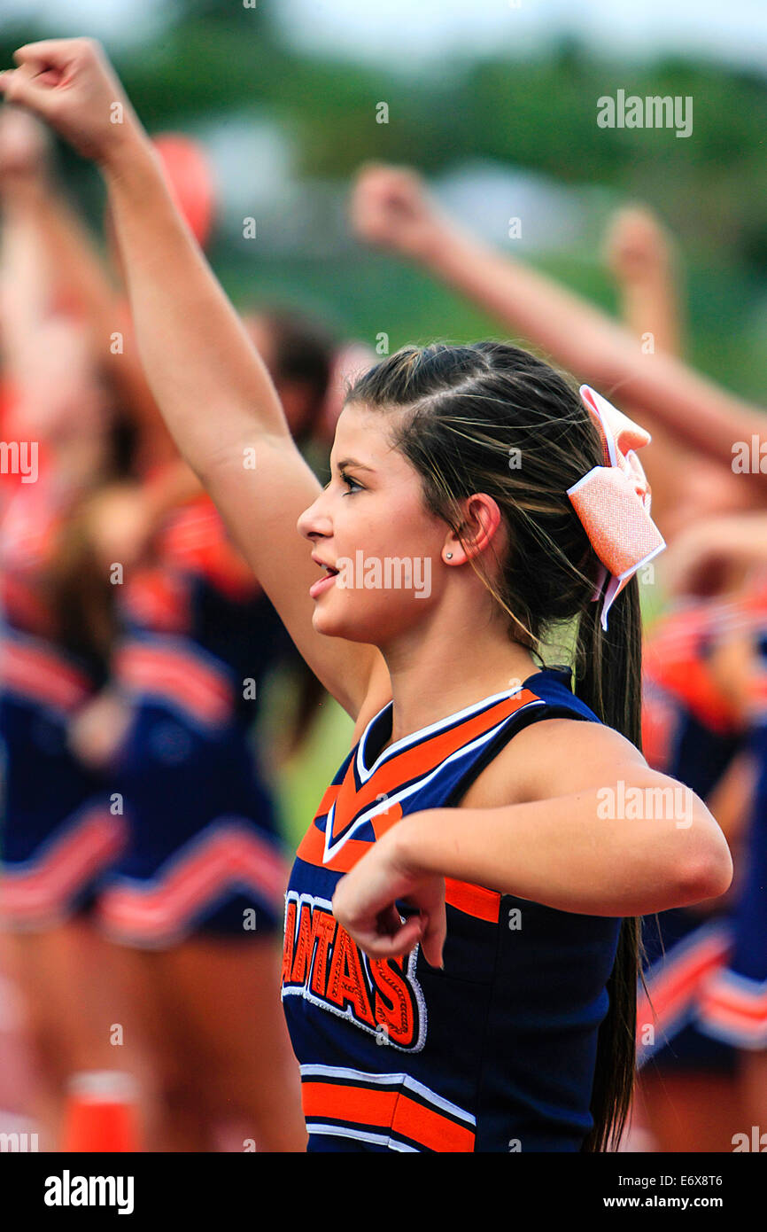 Junior Varsity High School female cheerleader stands in front of a crowd ready to rah rah! - Stock Image