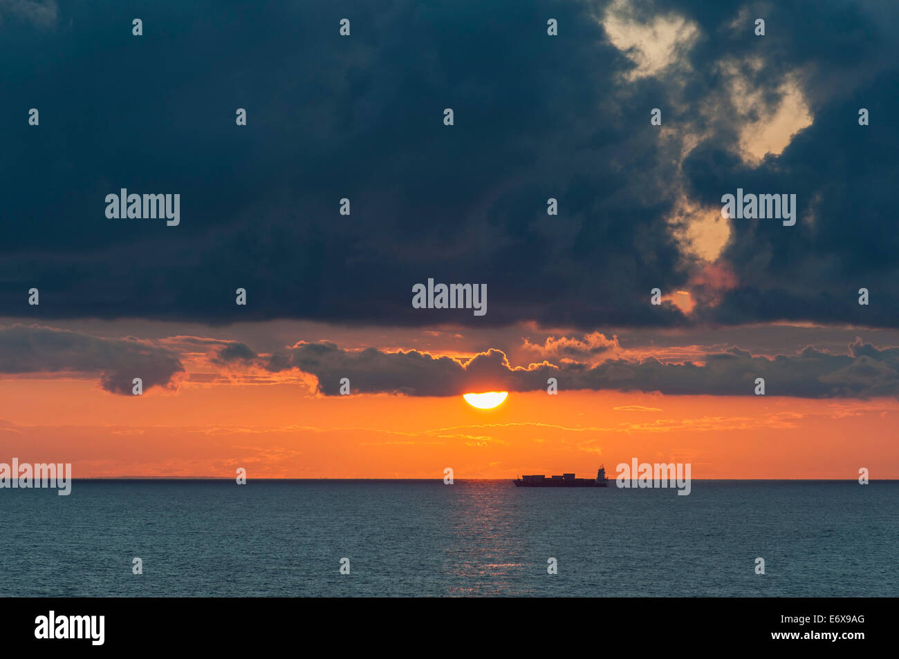 Baltic Sea at sunset, container ship at the back, clouds, off the island of Gotland, Sweden - Stock Image