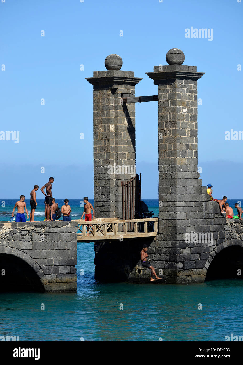 Local children and young people bathing at the Puente de las Bolas, stone gate outside the fort Castillo de San Stock Photo