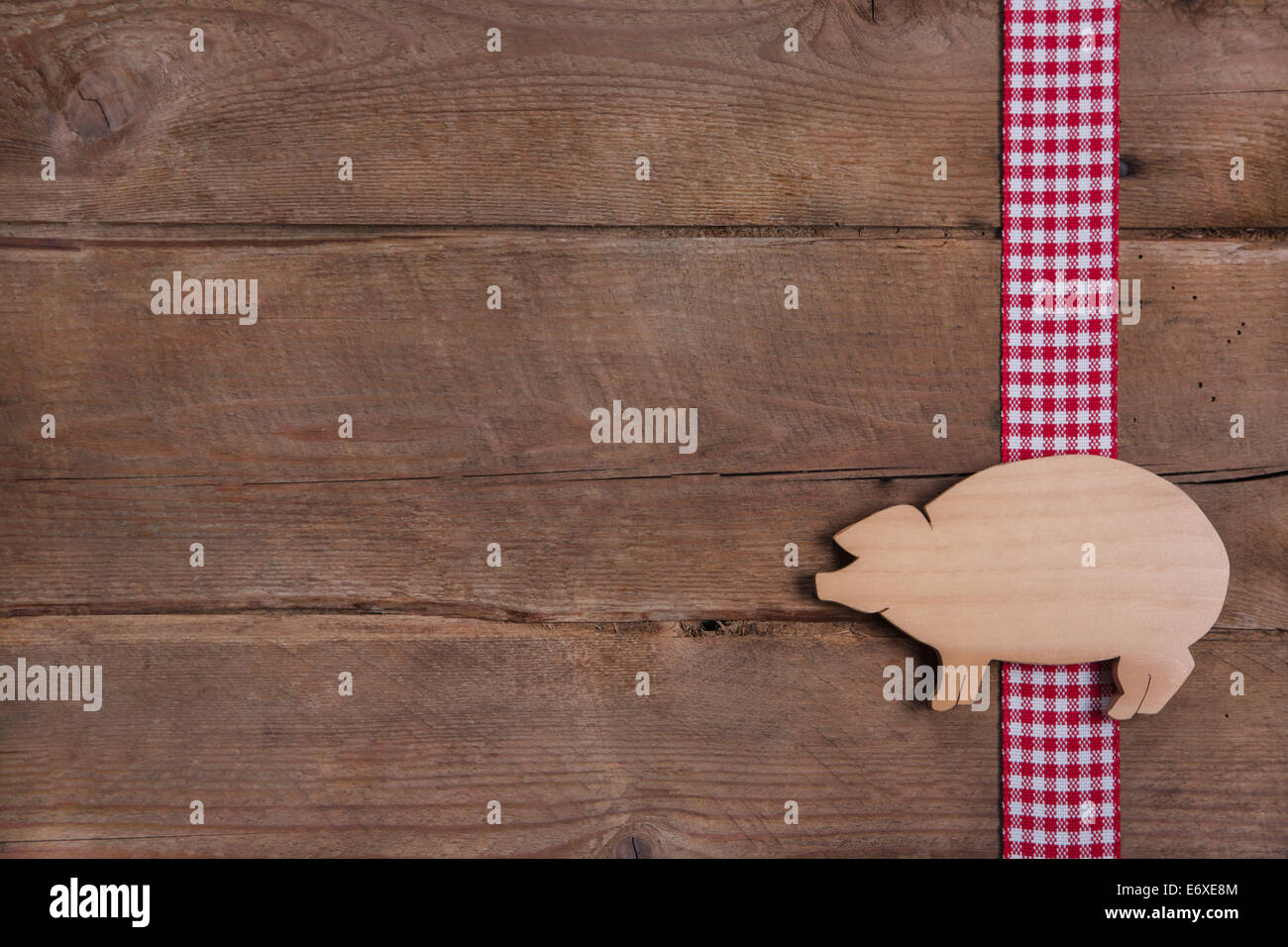 Wooden background with good luck pig on checkered ribbon or advertising for butcher - Stock Image