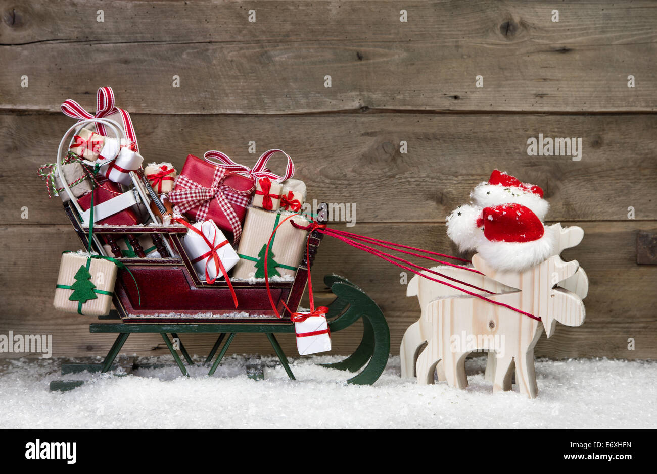 Christmas card decoration: elks pulling santa sleigh with presents on a wooden background - funny greeting card - Stock Image