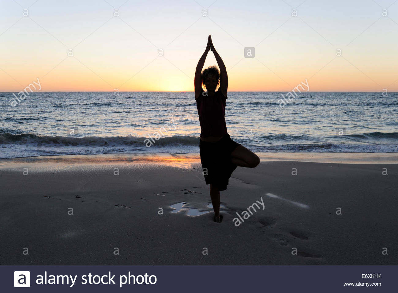 Yoga position, woman showing asana on the beach near Cervantes, Perth, Western Australia, WA, Indian Ocean, Australia - Stock Image